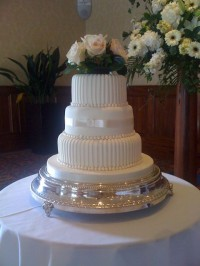 Three tier wedding cake with fresh flowers
